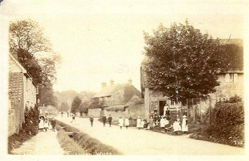 The High Street Circa 19th Century Rose Cottages on the left, Elm Cottage on the right. Note the thatched Granary Barn behind Elm Cottage.