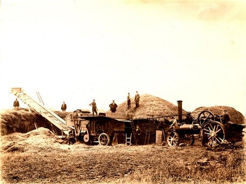 Group of men using machinery to move straw